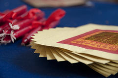 Red candles and Joss Paper (paper money). Short red candles on a blue table with a white wick and red lace next to a spiral stack of Joss Paper (paper money) Royalty Free Stock Photo