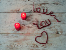 Red candles and love you letters on wooden background. close up. Text space. Gift for St. Valentine`s Day stock photo
