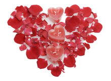 Red candles  in rose petals laid out in the form of heart. Royalty Free Stock Photography
