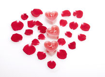 Red candles   in rose petals laid out in the form of heart. Stock Photography