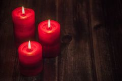 Red candles on rustic table stock photos