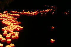 Red candles on the vagrant waters. Royalty Free Stock Photography