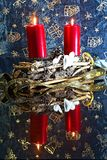 Red candles in wicker candlesticks and white hearts with mirroring. royalty free stock photography