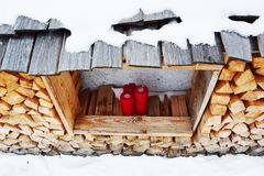 Red candles, wood logs and snow in Dolomity mountains, winter image stock photo