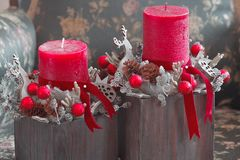Red candles and wooden Santa deers in Christmas table decoration Stock Photos