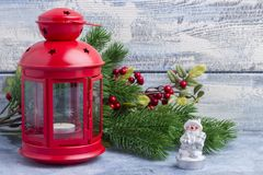 Red candlestick with a candle inside and a branch of a Christmas tree. Theme of the New Year and Christmas Royalty Free Stock Photo