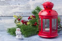 Red candlestick with a candle inside and a branch of a Christmas tree. Theme of the New Year and Christmas Stock Images