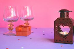 Red candlesticks with heart, present box and wine glasses on pink background. Valentine's Day theme or greeting card concept.  stock photo