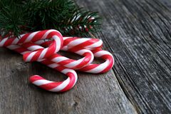 Red candy canes on old wooden table with fir branch. Copy space Royalty Free Stock Photography