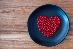 Red candy coated sunflower seeds in a heart shape on a rustic black plate on a wood background. For Valentine's Day stock photography