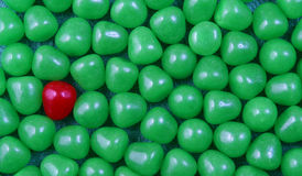 Red candy in green background. Solitary red candy sweet surrounded by green candy background stock photography