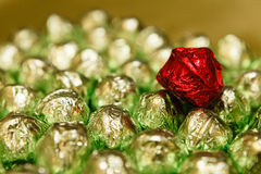 Red candy on green chocolates Stock Images