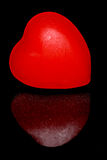 Red candy heart. On a black background with reflection royalty free stock photos