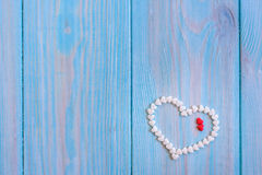Red candy heart laying on white painted rustic wooden background Royalty Free Stock Photography