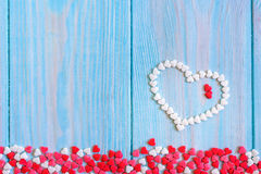 Red candy heart laying on white painted rustic wooden background Royalty Free Stock Image