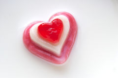 Red candy heart on a milk background. Concept Love. Red candy heart on a milk background Royalty Free Stock Photos