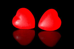 Red candy hearts. On a black background with reflection royalty free stock image