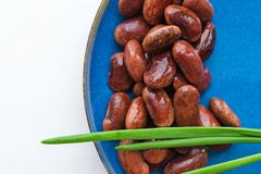 Red canned beans. With fresh green onions in blue ceramic plate over white background Stock Photo