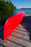Red Canoe. On A Wooden Cedar Dock On The Side Of A Lake Stock Photography