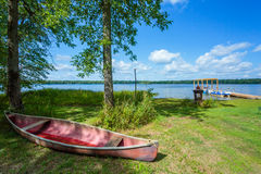 Red canoe on a beach of lake. Canada Stock Photo