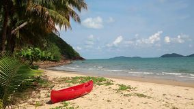 Red canoe on beautiful tropical beach. Red canoe on the beautiful tropical beach with palm trees stock footage