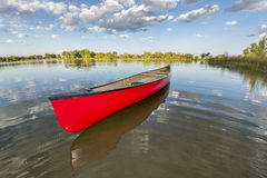 Red canoe on a calm lake. In a fisheye perspective, late summer in Fort Collins, Colorado Stock Images