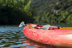 Red Canoe / Kayak and Paddle on River with Trees in Background Royalty Free Stock Images