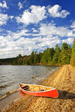 Red canoe on lake shore stock photos