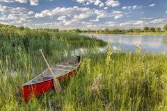 Red canoe on lake shore stock photography