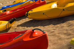Red canoe nose on sandy beach. Close-up of a canoe nose on sandy beach, more colourful canoes in background Stock Image