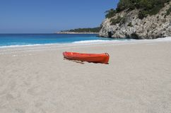 Red canoe on a large empty sandy beach against a turquoise sea. Red canoe with a paddle on the large empty sandy beach against a turquoise sea and a rocky shore Royalty Free Stock Image
