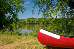 Red canoe on riverbank. A view of a red canoe resting on the quiet, wooded banks of a large river.  Place for name on bow Stock Photography