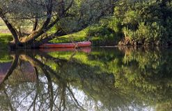 Red Canoe on Riverbank Stock Photos