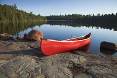 Red Canoe on Rocky Shore of Calm Lake with Pine Trees. A red canoe rests on a rocky shore of a calm blue lake in the Boundary Waters of Minnesota Royalty Free Stock Images
