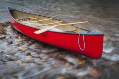 Red canoe on a shallow rocky river Royalty Free Stock Image