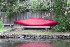 Red canoe on the side of a river Royalty Free Stock Photos