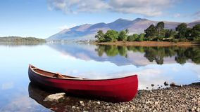 Red Canoe. A timelapse video of a red canoe on the banks of Derwentwater in the English Lake District National Park. Skiddaw the fourth highest mountain in stock video footage
