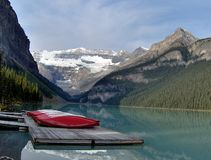 Red Canoes on Dock at Lake Louise Alberta. Candy red canoes rest on a weathered dock on Lake Louise in Banff National Park Alberta.  The surrounding mountains Royalty Free Stock Images