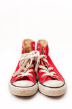 Red canvas sneakers. A used pair of red canvas sneakers which come up to your ankles. They are bright red in color and hhave white rubber covers on the toes and royalty free stock photo