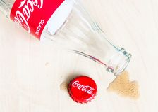 Red cap, Coca-Cola bottle and puddle of drink. MOSCOW, RUSSIA - APRIL 4, 2019: red crown cap, empty bottle from Coca-Cola beverage and spilled puddle on wooden stock images