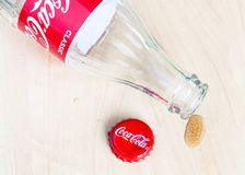 Red cap, empty Coca-Cola bottle and drop of drink. MOSCOW, RUSSIA - APRIL 4, 2019: red crown cap, empty bottle from Coca-Cola beverage and drop of drink on stock photo