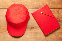 Red cap, pencil and dairy on wooden background Stock Images