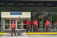 Red Cap Porters with luggage trolleys at Airport. Montego Bay, Jamaica - June 06 2015: Red Cap Porters with luggage trolleys outside Departures at Sangster stock photo