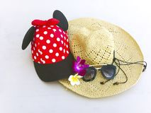 Red cap with white polka dots, straw hat, flowers and sunglasses. Red cap with white polka dots decorated with red bow and black fabric , straw hat with black stock image