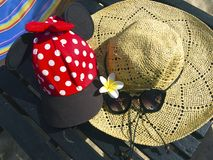 Red cap with white polka dots, straw hat, flowers and sunglasses. Red cap with white polka dots decorated with red bow and black fabric , straw hat with black royalty free stock photo