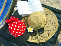 Red cap with white polka dots, straw hat, flowers, book and sung. Red cap with white polka dots decorated with red bow and black fabric , straw hat with black stock photography