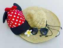Red cap with white polka dots, straw hat, flowers and sunglasses. Red cap with white polka dots decorated with red bow and black fabric , straw hat with black royalty free stock photography