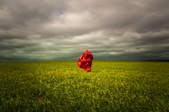 Red Cape mystical figure in the fields of green. Royalty Free Stock Photography