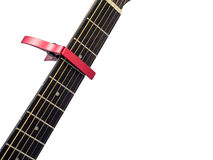 Red capo on guitar fingerboard, white background Stock Images
