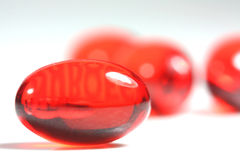 Red capsule pills. Bright red liquid capsule pill close up royalty free stock photo